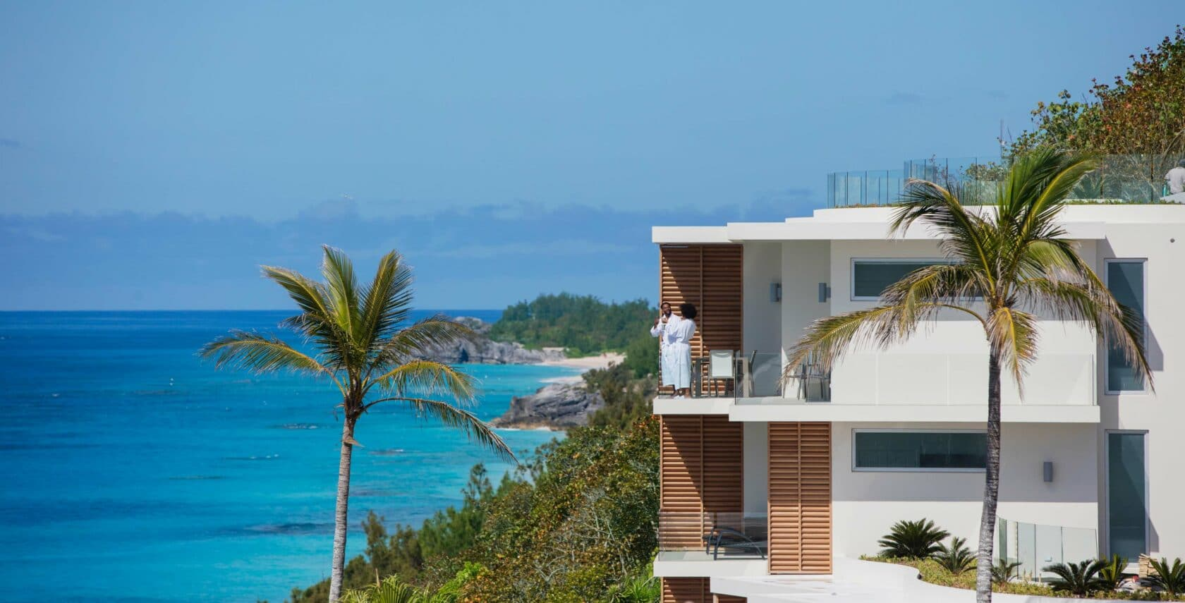 A couple on a balcony of a resort overlooking the ocean.