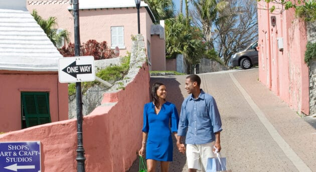 A couple walking down a street with pink buildings.
