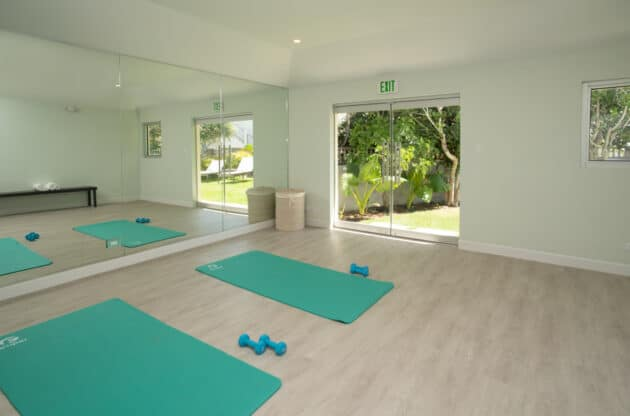 A yoga studio with a large mirror and two mats on the floor.