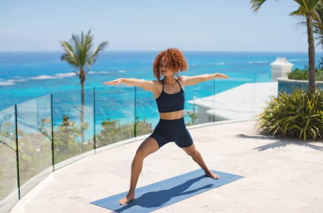 A woman practicing yoga outside, with an ocean view in the background.