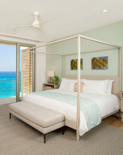 A bedroom with a canopy bed and glass doors with an ocean view.