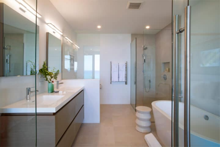 A bathroom with two sinks, a bath tub, and a shower booth.