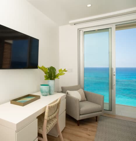 A desk with a TV on the wall in front of it, along with sliding glass doors displaying an ocean view.