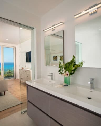 Two bathroom sinks and a glass door leading to a different room.