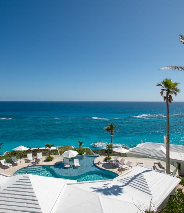 An aerial view of an outdoor pool with a poolside seating area, all overlooking an ocean.