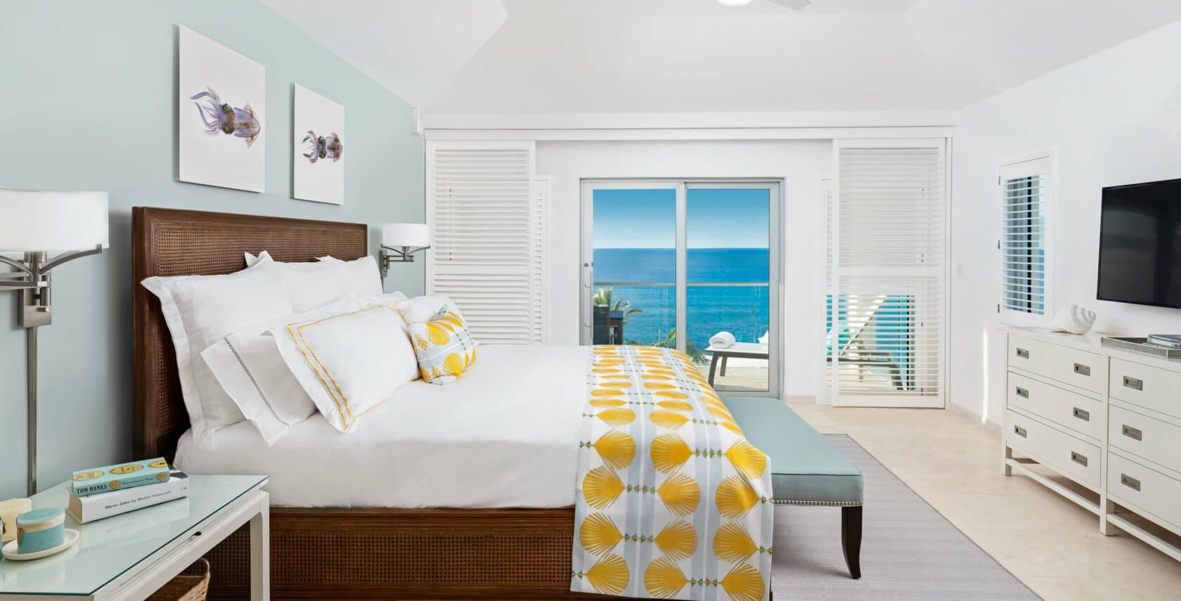A bedroom with large glass doors showing a view of the ocean.