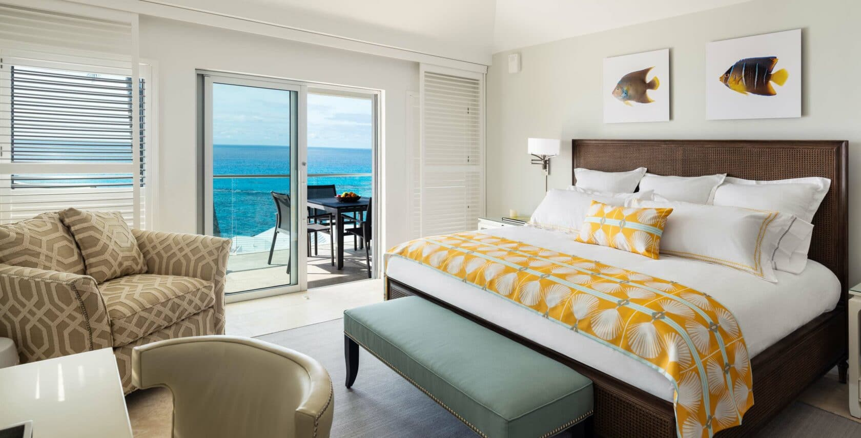 A bedroom with sliding glass doors leading to a deck with an ocean view.