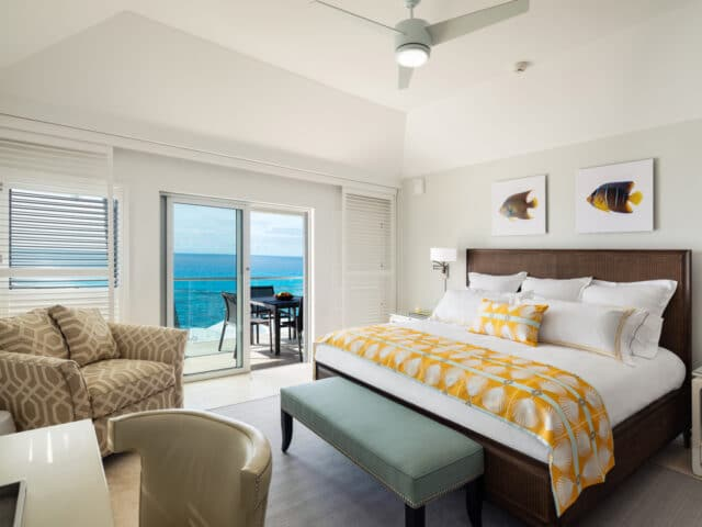 A bedroom with glass sliding doors leading to an outdoor deck.