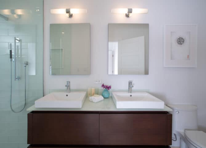 Two bathroom sinks with two mirrors.