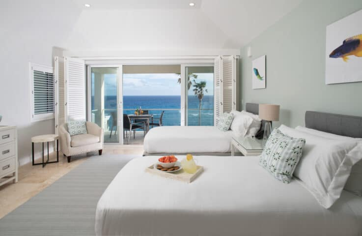 A bedroom with two beds and sliding glass doors with an ocean view.