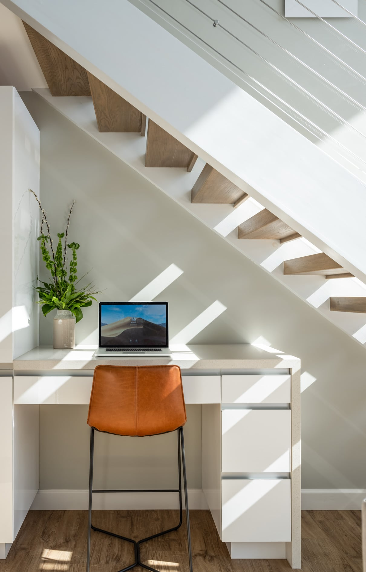 A desk with an open laptop below a staircase.