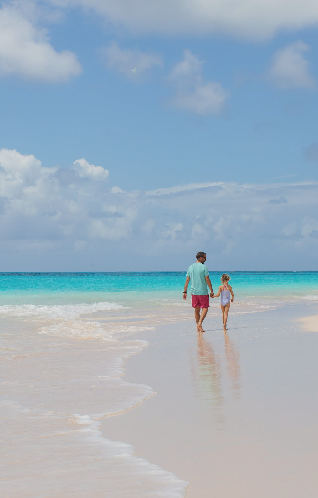 A child holding hands and walking on a beach with her father.