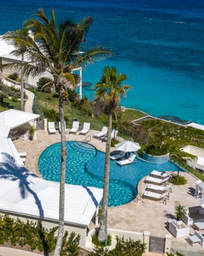 An aerial view of an outdoor pool overlooking the ocean.
