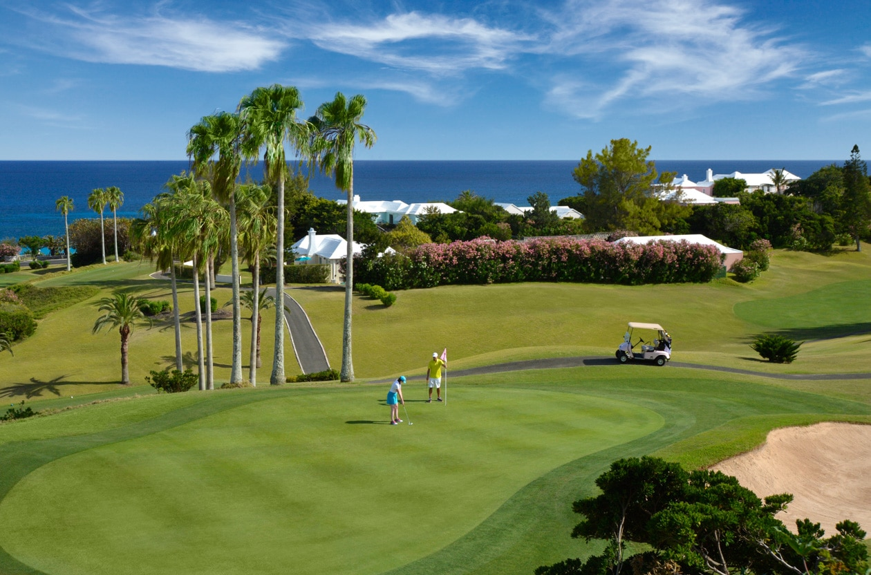 A golf course with palm trees and the ocean in the background.