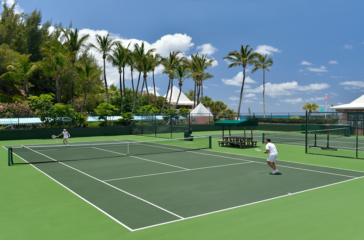 Two people playing tennis at a tennis court with palm trees in the background.