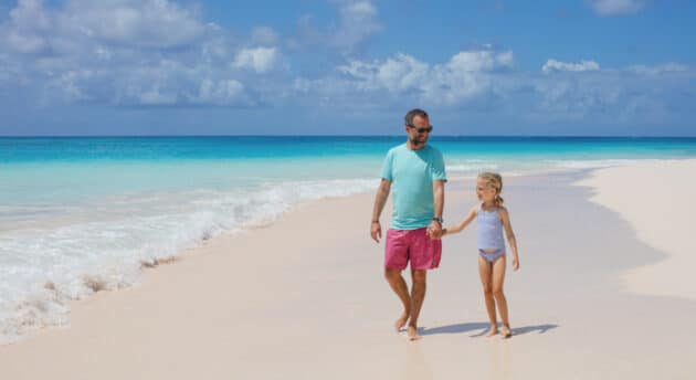 A father and daughter holding hands and walking on a beach.