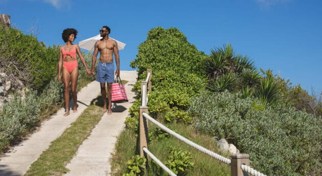 A couple wearing bathing suits, holding hands and walking down a path.