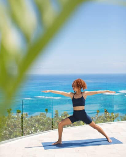 A woman practicing yoga on a deck overlooking the ocean.