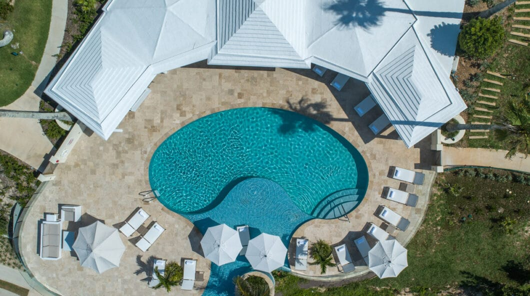A birds eye view of a swimming pool with parasols and a seating area around it.