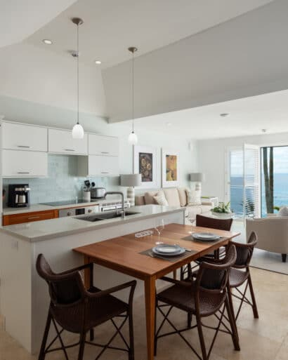 A kitchen and dining area with a living room in the background.